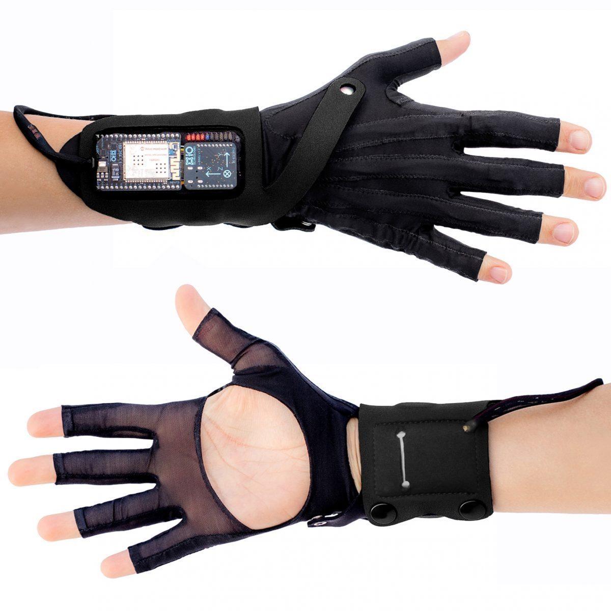 Die MIMUGloves sind schwarze Handschuhe ohne Fingerkuppen und offener Handfläche. Am Handgelenk sitzt ein Monitor, der z.B. Klangqualität oder Volumen anzeigt.
