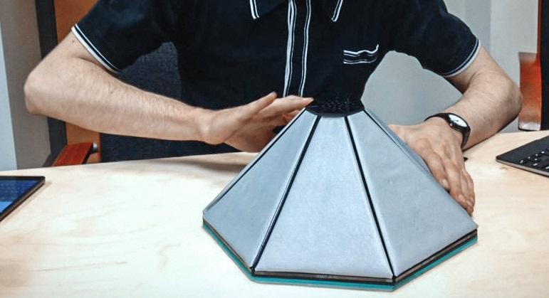 Ein Mensch berührt mit zwei Händen ein dreidimensionales Touchpad mit sieben Seiten.