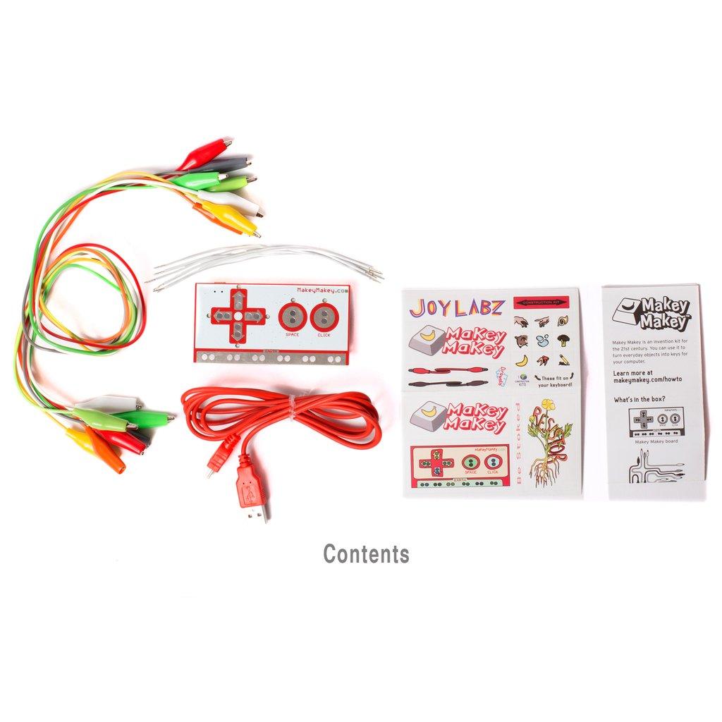 Ganz links ist ein Strang bunter Kabel mit Krokodilklammern. Rechts daneben liegt ein Controller mit Steuerkreuz und Tasten, einem roten USB-Kabel. Daneben liegen zwei Zettel mit Beschreibungen und Anleitungen.