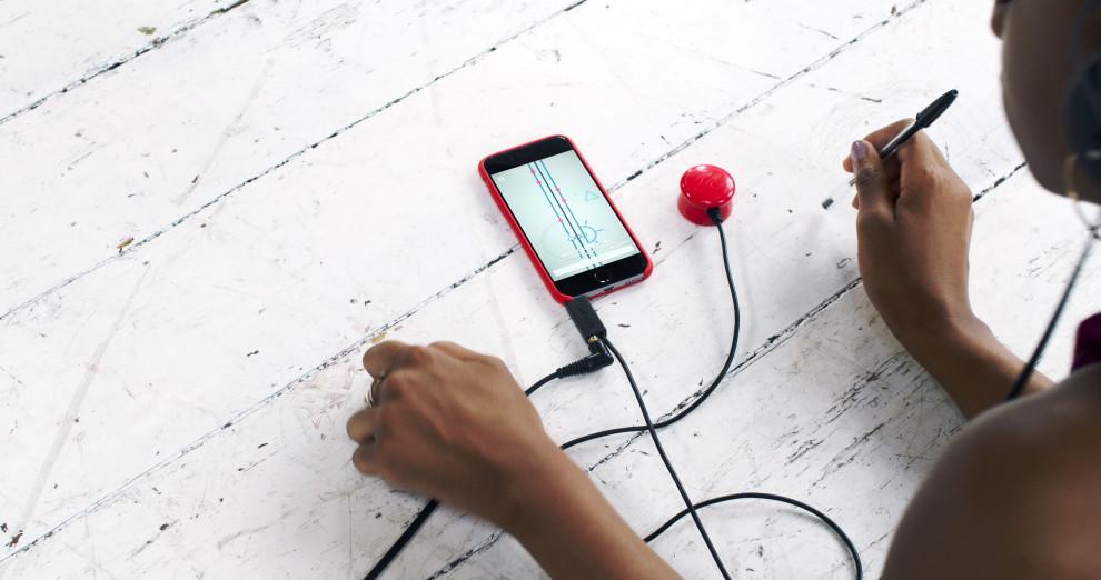 Eine Person sitzt an einem Tisch, auf dem ein Smartphone liegt. Das Telefon hat Kopfhörer angeschlossen und ein Kabel, das zu einem roten Knopf führt.