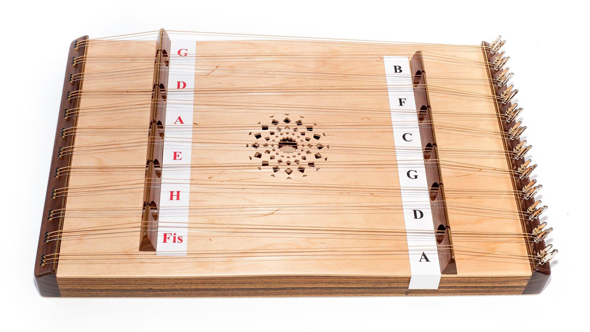 Ein flaches Holzbrett, das von rechts nach links an Metallstiften viele Saiten über zwei Holzstege gespannt hat. An deren Seiten befinden sich links und rechts jeweils verschiedene Notenbezeichnungen. In der Mitte ist ein verziertes Loch im Holz.