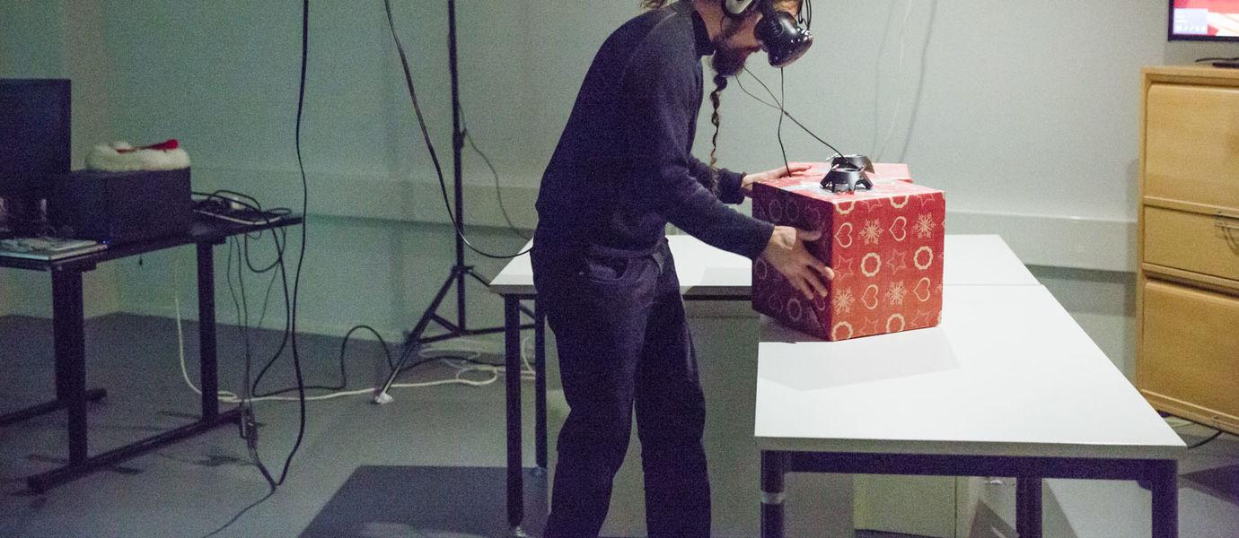 Ein Mann hat Kopfhörer auf und eine VR-Brille. Vor ihm auf dem Tisch stehen zwei rote Pakete. Darauf stehen vermutlich Kameras, die der Mann ansieht. Per Kabel ist er mit ihnen verbunden.